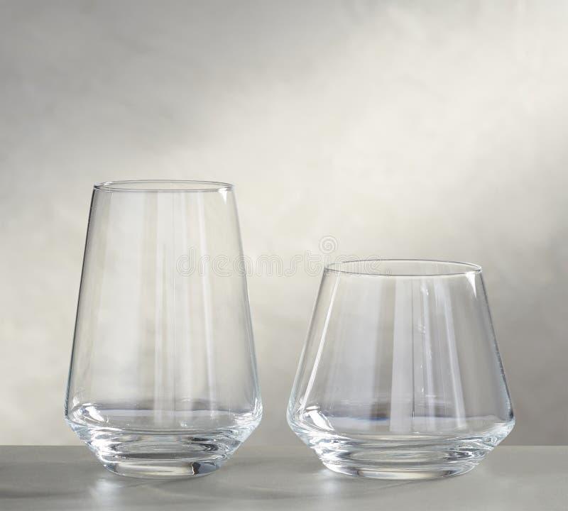 Verres de vin vides sur la table en verre et le fond blanc photo stock