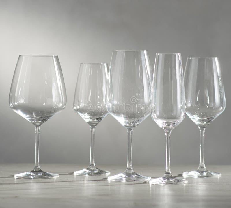 Verres de vin vides sur la table en verre et le fond blanc photos stock