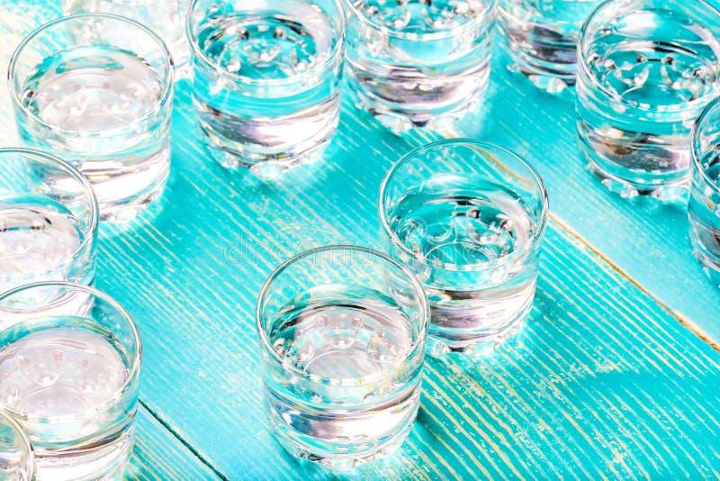 Verres en verre chaotiquement disposés de dessous une boisson alcoolisée sur une table bleue image stock