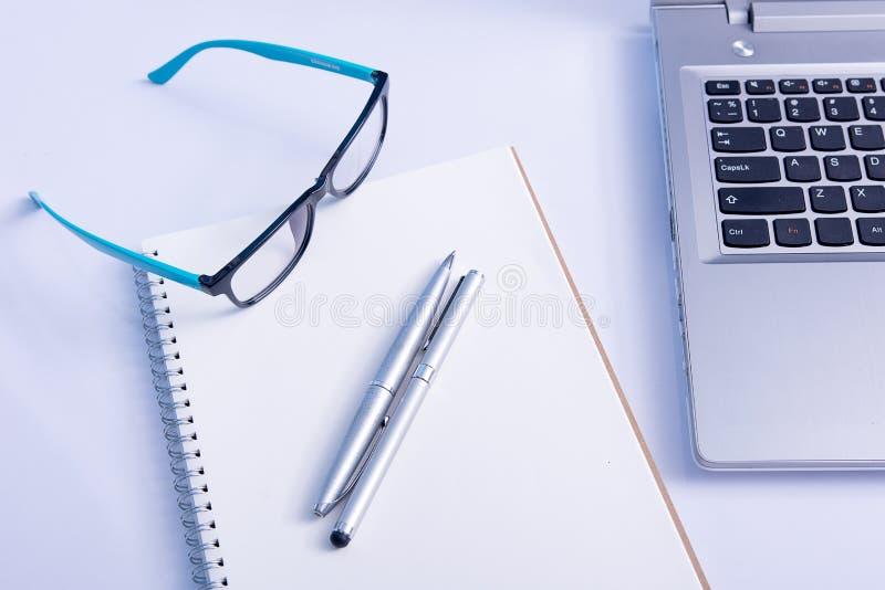 Verres et carnet et ordinateur portable vides dans le bureau photographie stock