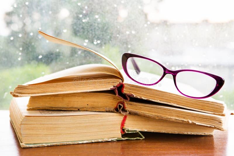 Verres et livres de lecture sur la fenêtre pluvieuse photographie stock libre de droits