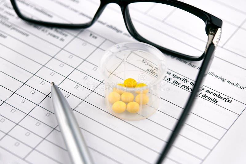 Verres, pilules jaunes en verre gradué et stylo sur la forme médicale de questionnaire photographie stock libre de droits