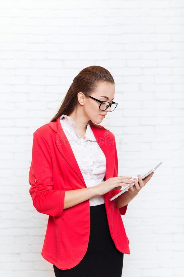 Verres rouges de veste d'usage d'écran tactile de tablette d'utilisation de femme d'affaires image stock