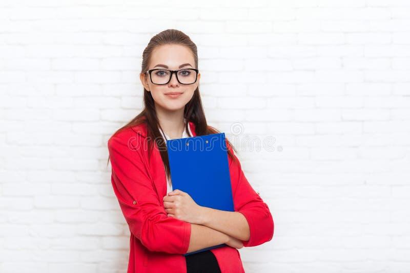 Verres rouges de veste d'usage de sourire de dossier de prise de femme d'affaires image libre de droits