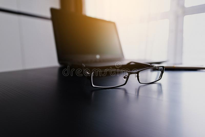 Verres sur l'ordinateur portable avec le stylo sur le bureau photos libres de droits
