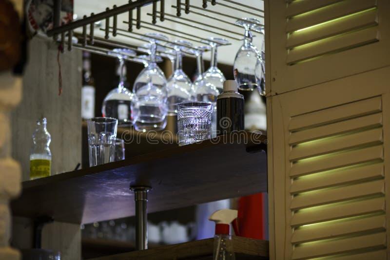Verres suspendus dans une barre, verres pour le vin et champagne images libres de droits