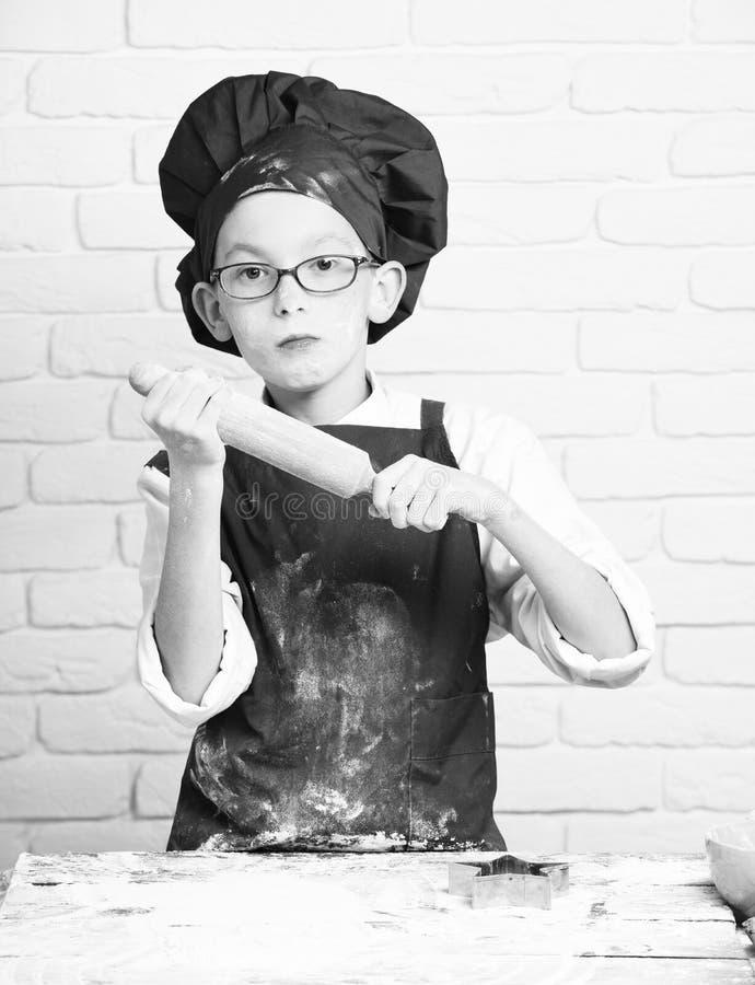 Verres tenant la table proche avec la goupille sur le fond blanc de mur de briques, garçon mignon souillé de chef de cuisinier photos stock