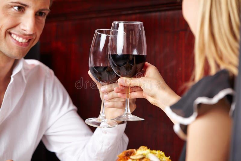 Verres tintants de couples de vin rouge photo stock