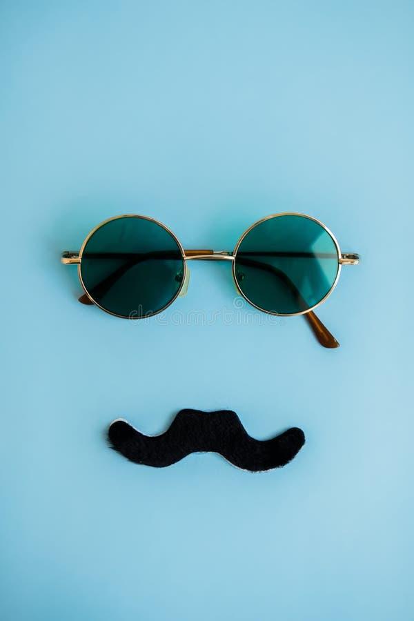 Verres verts ronds et moustache noire sur le fond bleu Le concept du jour du ` s de père du ` s de l'homme, mois de cancer de la  images stock