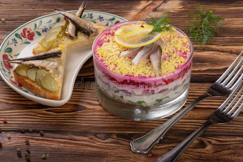 Verrin-Glas mit köstlichen russischen Salatheringen unter Pelzmantel vom Gemüse auf hölzernem bacground stockfotos