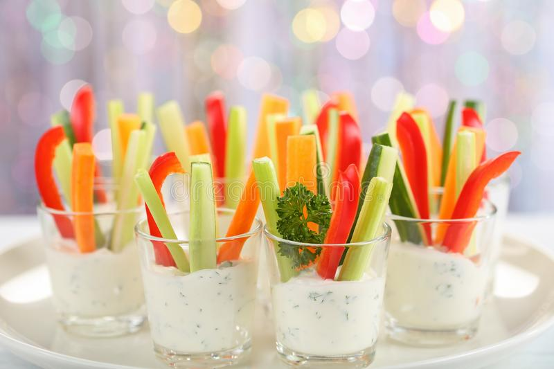 Verrines appetizer with carrot, cucumber, celery and red bell pepper sticks in glasses on platter at bokeh background, royalty free stock photos