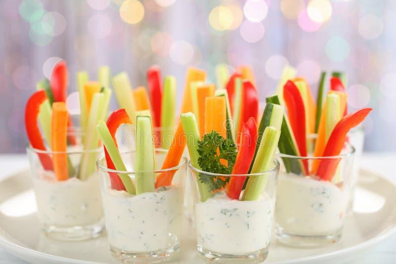 Verrinesvoorgerecht met wortel, komkommer, selderie en rode groene paprikastokken in glazen op schotel bij bokehachtergrond, royalty-vrije stock foto's