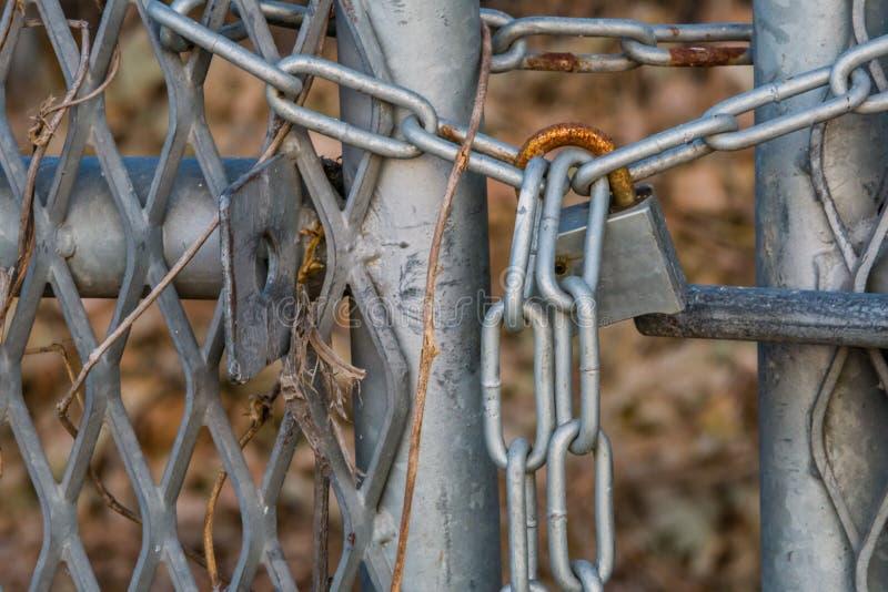 Verrostendes Vorhängeschloß auf Tor des Kettengliedzauns stockbild