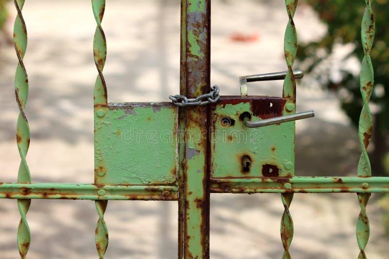 Verrostete teilweise Metalltüreingang mit verdrehten grünen Metallstangen und verrosteten dem Verschluss, die mit starker Kette g stockbilder