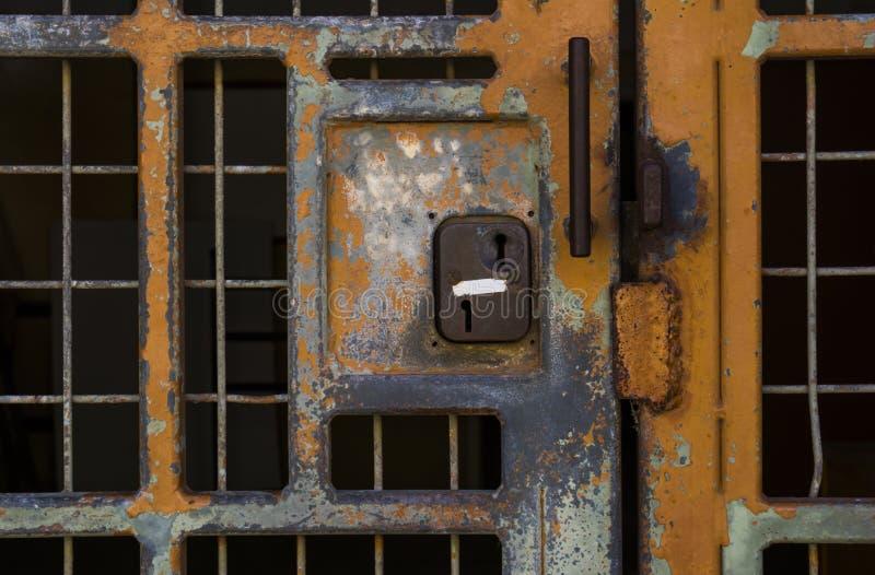 Verrouillé dedans ou verrouillé ? Vieille porte verrouillée de grille en métal photo stock