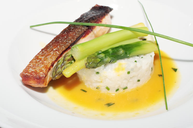 Verrukkelijke gebakken vissen met rijst en een asperge stock afbeeldingen