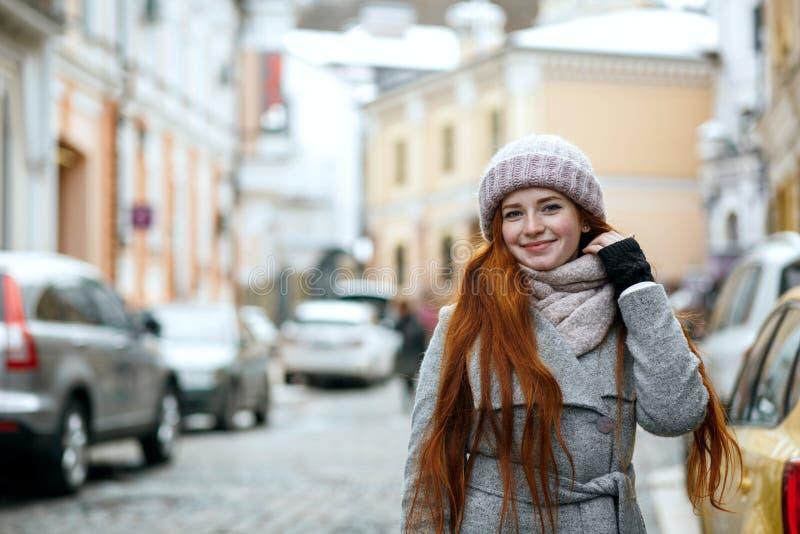 Verrukkelijke rode haired vrouw die het warme de winterkleren lopen dragen stock foto's