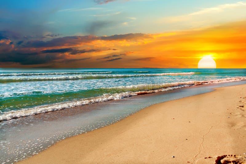 verrukkelijke zonsopgang over de oceaan en een verlaten zandig strand royalty-vrije stock afbeelding