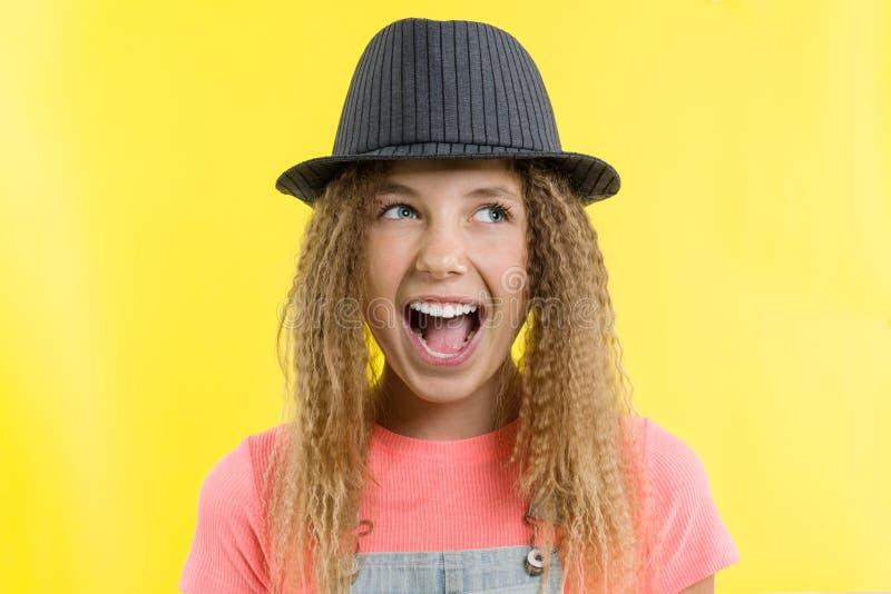 Verrukking, geluk, vreugde, overwinning, succes en geluk Tienermeisje op een gele achtergrond royalty-vrije stock afbeeldingen