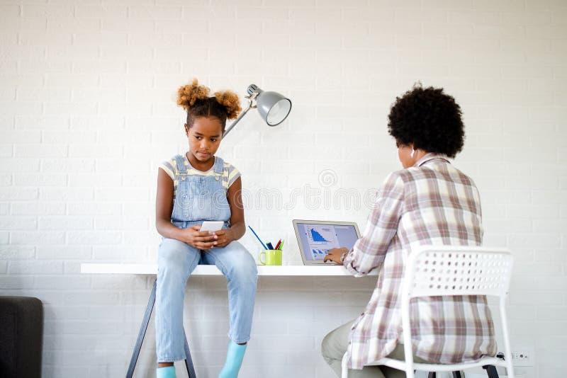 Verrukt triest kind op zoek naar aandacht van drukke werkende ouders stock afbeeldingen