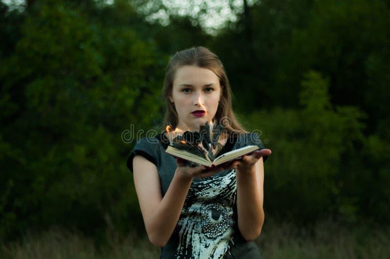 Versão clássica do estilo das bruxas Uma menina em seus braços é um livro ardente do fogo fotografia de stock royalty free