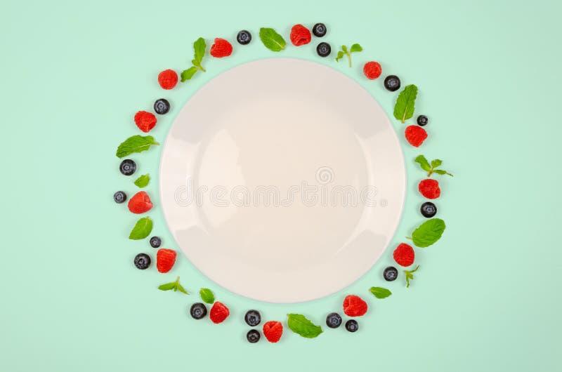 Vers bosbessen, frambozen en muntblad op hoogste mening met witte plaat en pastelkleur groene kleurenachtergrond voor gezond voed royalty-vrije stock foto's