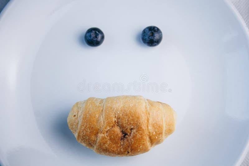 Vers bosbessenbessen en croissant in de vorm van een gezicht met een smileon een wit plaatclose-up ontbijt van wilde bessen exemp stock foto