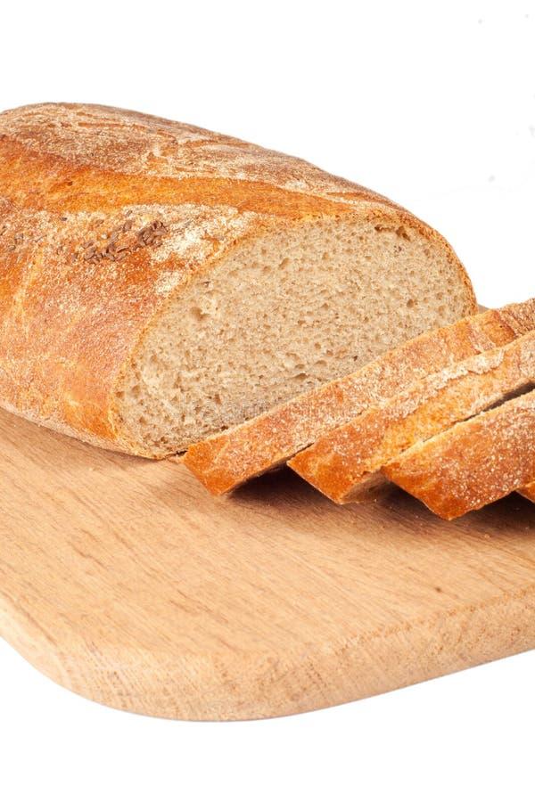 Vers brood dat op een houten hakbord wordt gesneden stock afbeelding