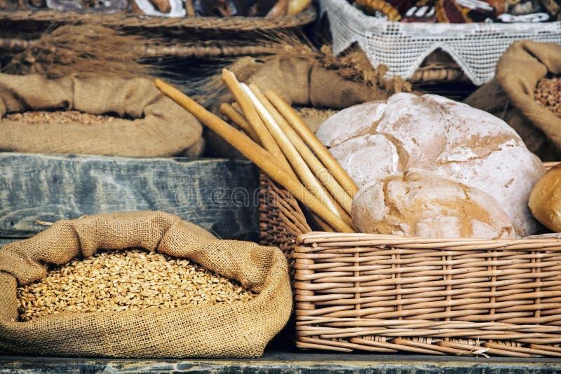 Vers brood met gebakje in de rieten mand en korrel in de bedelaars stock foto's