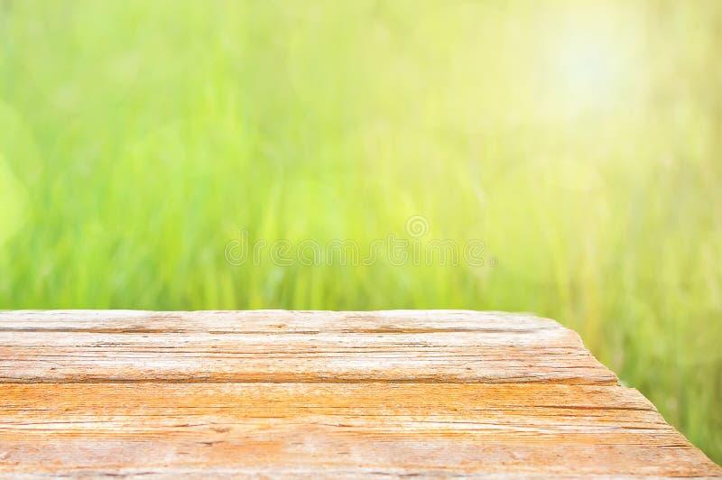 Vers de lente groen gras met groen bokeh en zonlicht en houten vloer Natuurlijke achtergrond Exemplaar-ruimte voor tekst royalty-vrije stock afbeelding