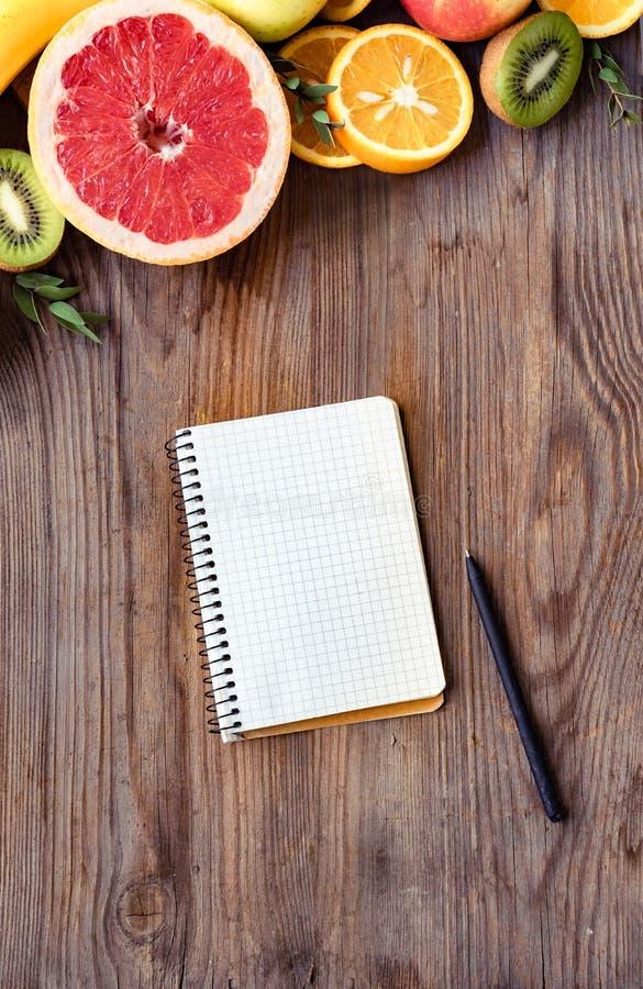 Vers de zomervruchten en notitieboekje op bruine houten achtergrond, hoogste verticale mening stock afbeeldingen