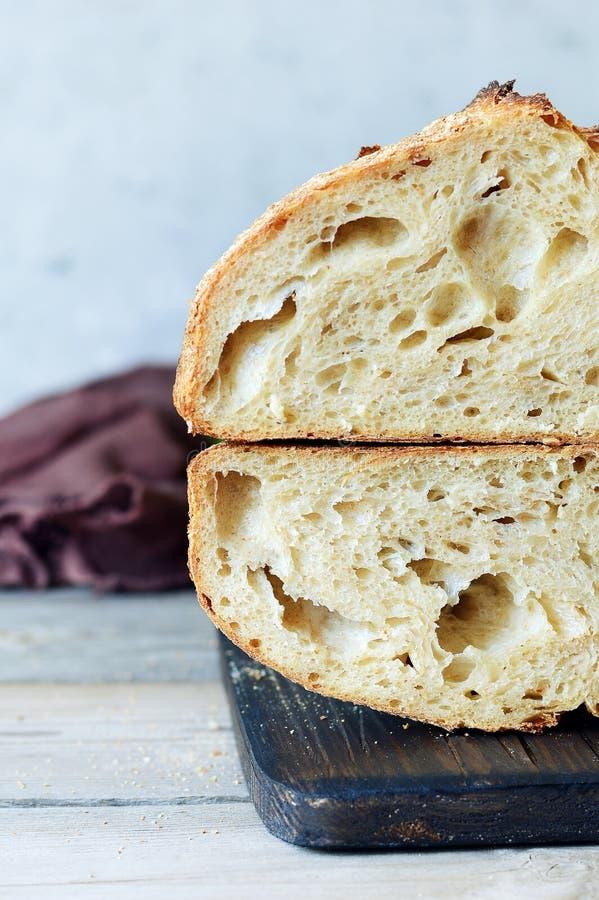 Vers eigengemaakt brood op de blauwe achtergrond kernachtig Het Frans kweekte Brood bij zuurdeeg Ongedesemd brood stock fotografie