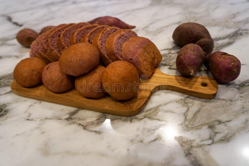 Vers eigengemaakt gebakken purper Japans bataatbrood in gesneden brood en broodjes op houten scherpe raad op witte marmeren lijst royalty-vrije stock foto's