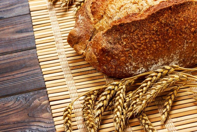 Vers Eigengemaakt Geheel Brood met tarwe op een houten Achtergrond stock fotografie