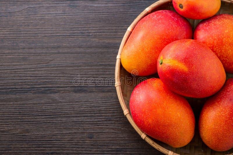 Vers en mooi mangofruit in een bamboemand op een donkere houten achtergrond, exemplaar spacetext ruimte, spatie voor tekst stock fotografie