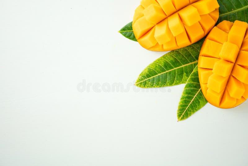 Vers en mooi mangofruit met gesneden gedobbelde mangobrokken op een lichtblauwe achtergrond, exemplaar spacetext ruimte stock afbeeldingen