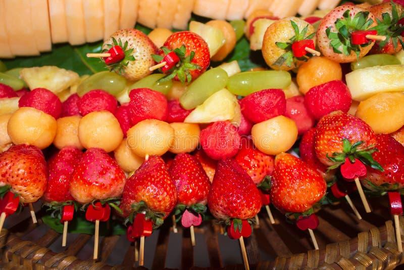 Vers fruit met heldere kleuren, als barbecue, met aardbeien, ananas, druiven, watermeloen Op bamboelijst stock afbeelding