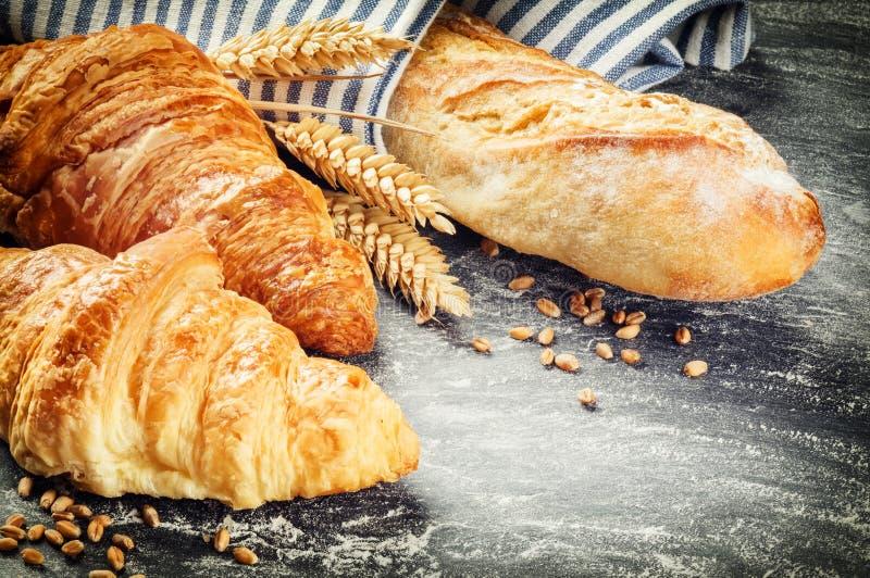 Vers gebakken baguette en croissants in het rustieke plaatsen stock fotografie