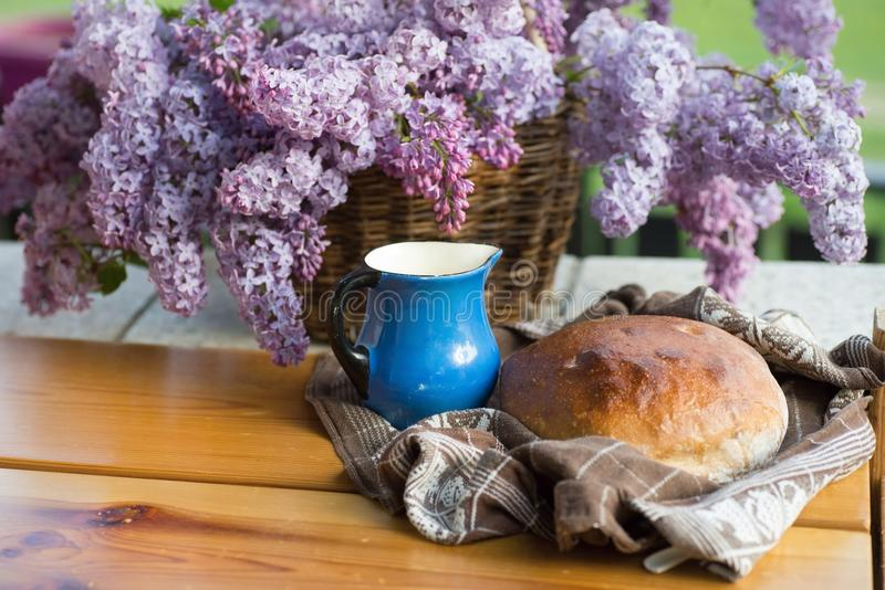 Vers gebakken brood, in handdoek, blauwe waterkruik en tot bloei komende sering stock afbeelding