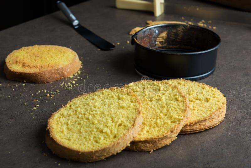 Vers gebakken die biscuitgebak in vier lagen, met de vorm van het cakebaksel en spatel wordt gesneden royalty-vrije stock afbeelding