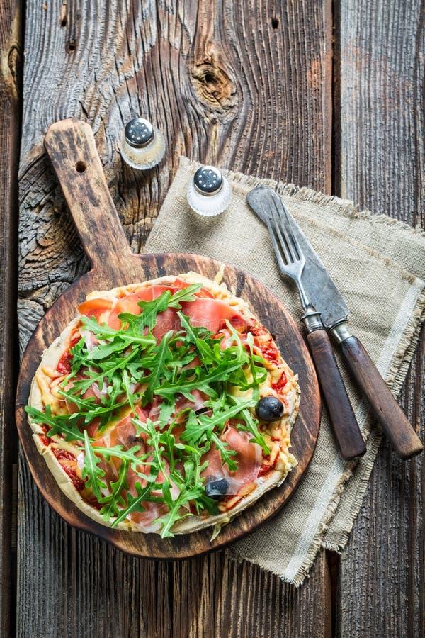 Vers gebakken die pizza op bakseldocument wordt verdeeld en wordt gegeven royalty-vrije stock foto's
