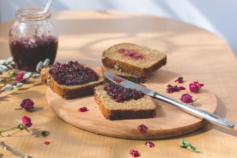 Vers gebakken eigengemaakt gezond brood met blackcurrant jam stock foto