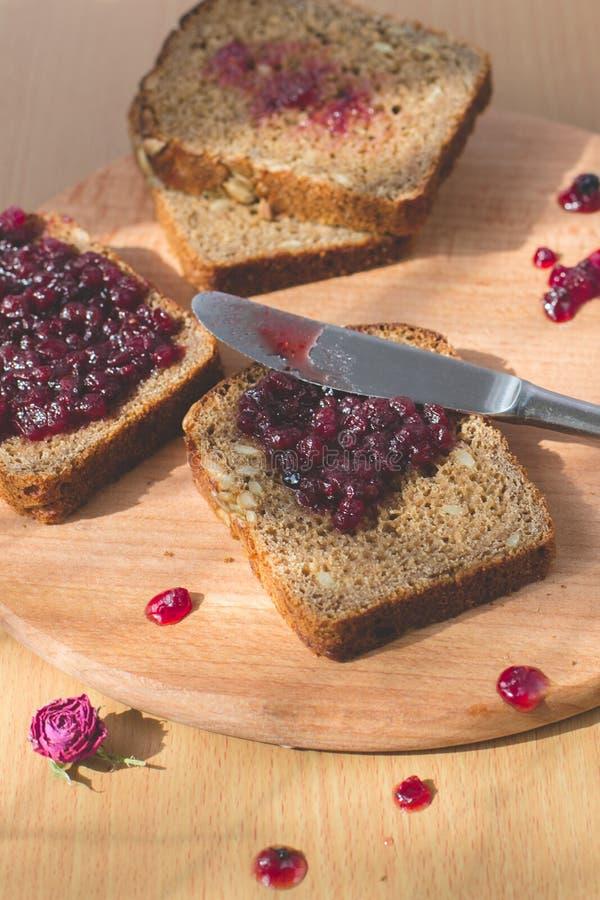 Vers gebakken eigengemaakt gezond brood met blackcurrant jam - eigengemaakte marmelade met verse organische vruchten van tuin In  stock afbeelding