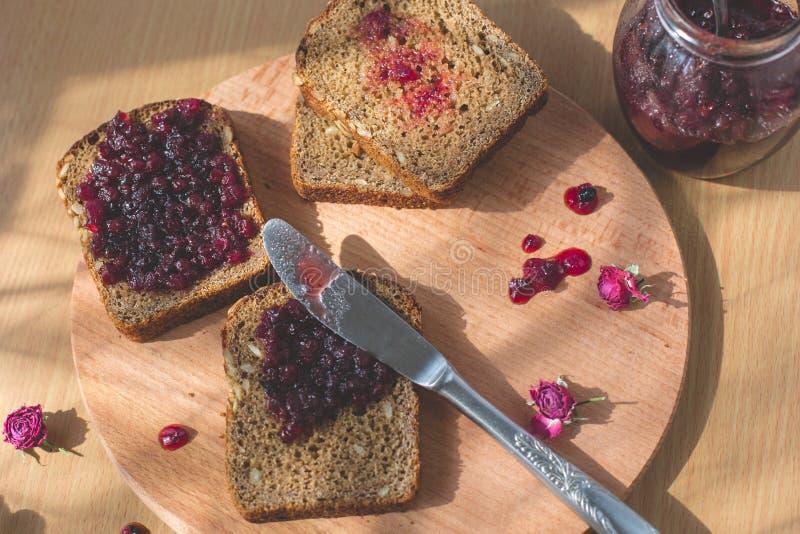 Vers gebakken eigengemaakt gezond brood met blackcurrant jam - eigengemaakte marmelade met verse organische vruchten van tuin In  stock foto