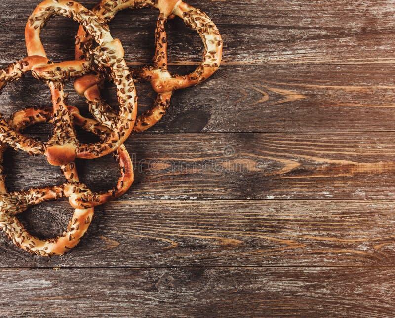 Vers gebakken eigengemaakte pretzels met zaden op rustieke houten lijst Hoogste mening, lichteffect royalty-vrije stock fotografie