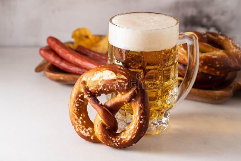 Vers gebakken eigengemaakte zachte pretzel met zout op witte lijst met glas bier stock fotografie