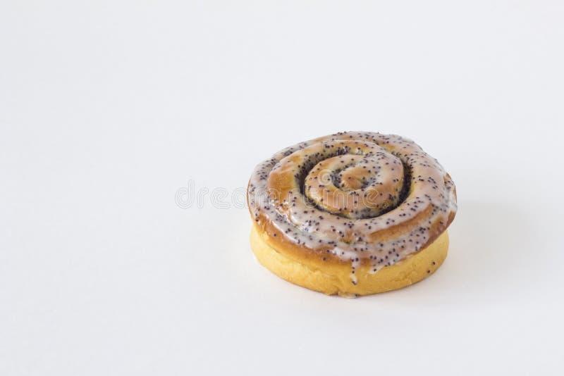 Vers gebakken geel bruin broodje met room en papaverzadenclose-up met schaduwen op een witte achtergrond royalty-vrije stock foto's