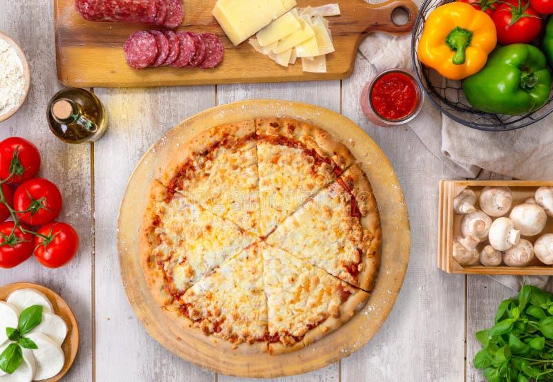 Vers gebakken gehele kaaspizza op houten raad en lijst, met kleurrijke ingrediënten, lucht hoogste mening royalty-vrije stock fotografie