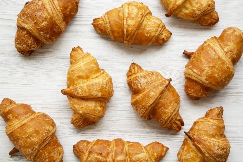 Vers gebakken gouden croissants op witte houten, hoogste mening Van hierboven stock afbeeldingen