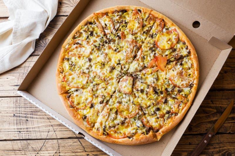 Vers gebakken pizza in een kartonvakje op een houten lijst royalty-vrije stock fotografie